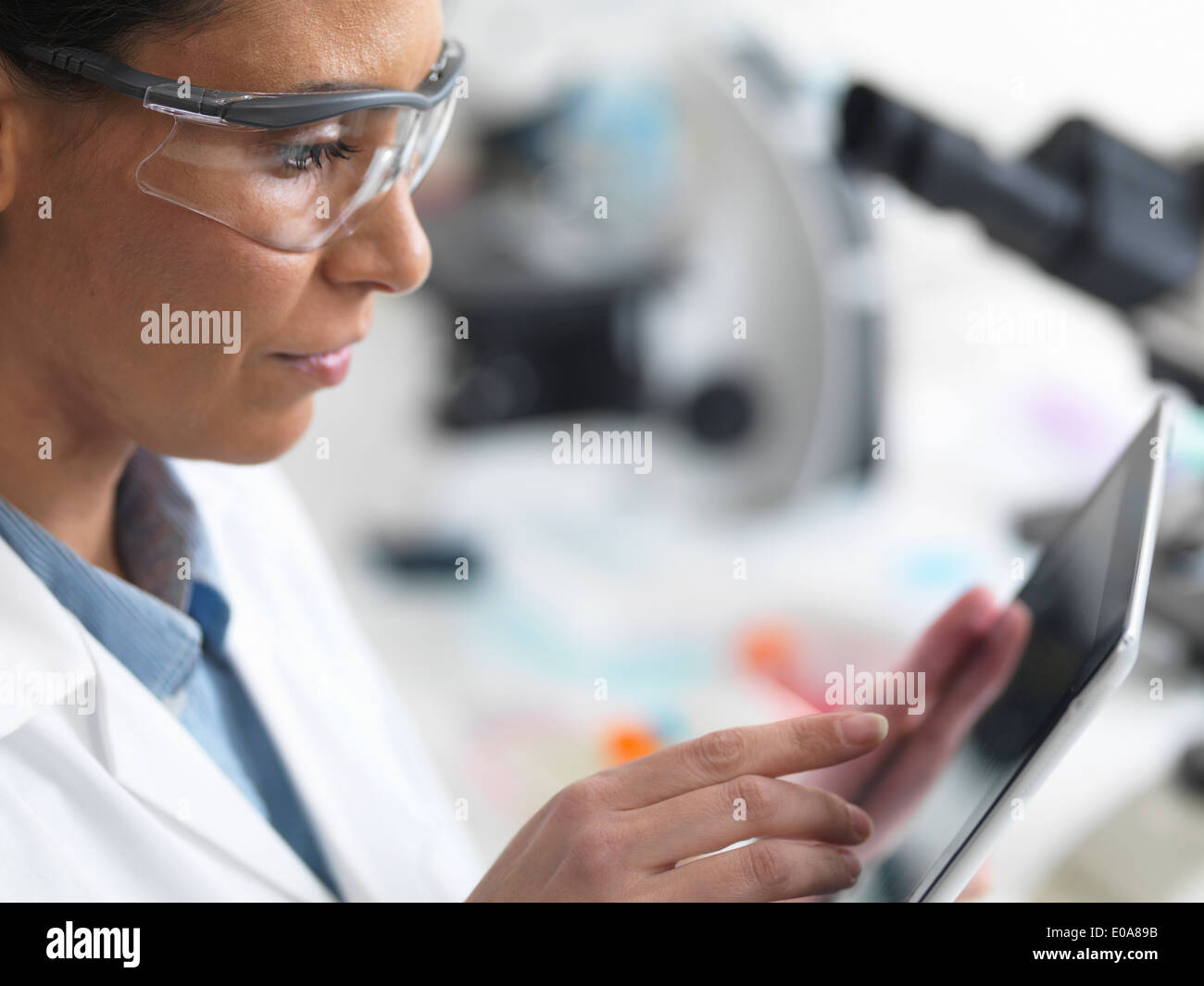 Female scientist viewing test results on a digital tablet in lab - Stock Image