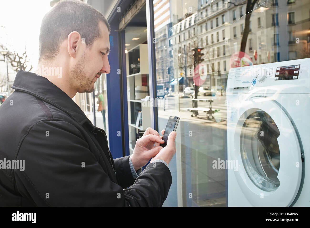 Mid adult man checking out washing machine in shop using smartphone - Stock Image