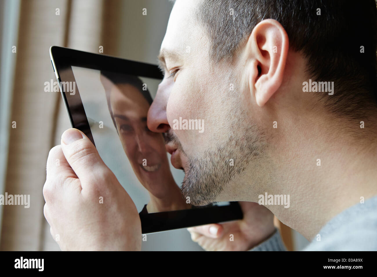 Mid adult man kissing screen of digital tablet - Stock Image