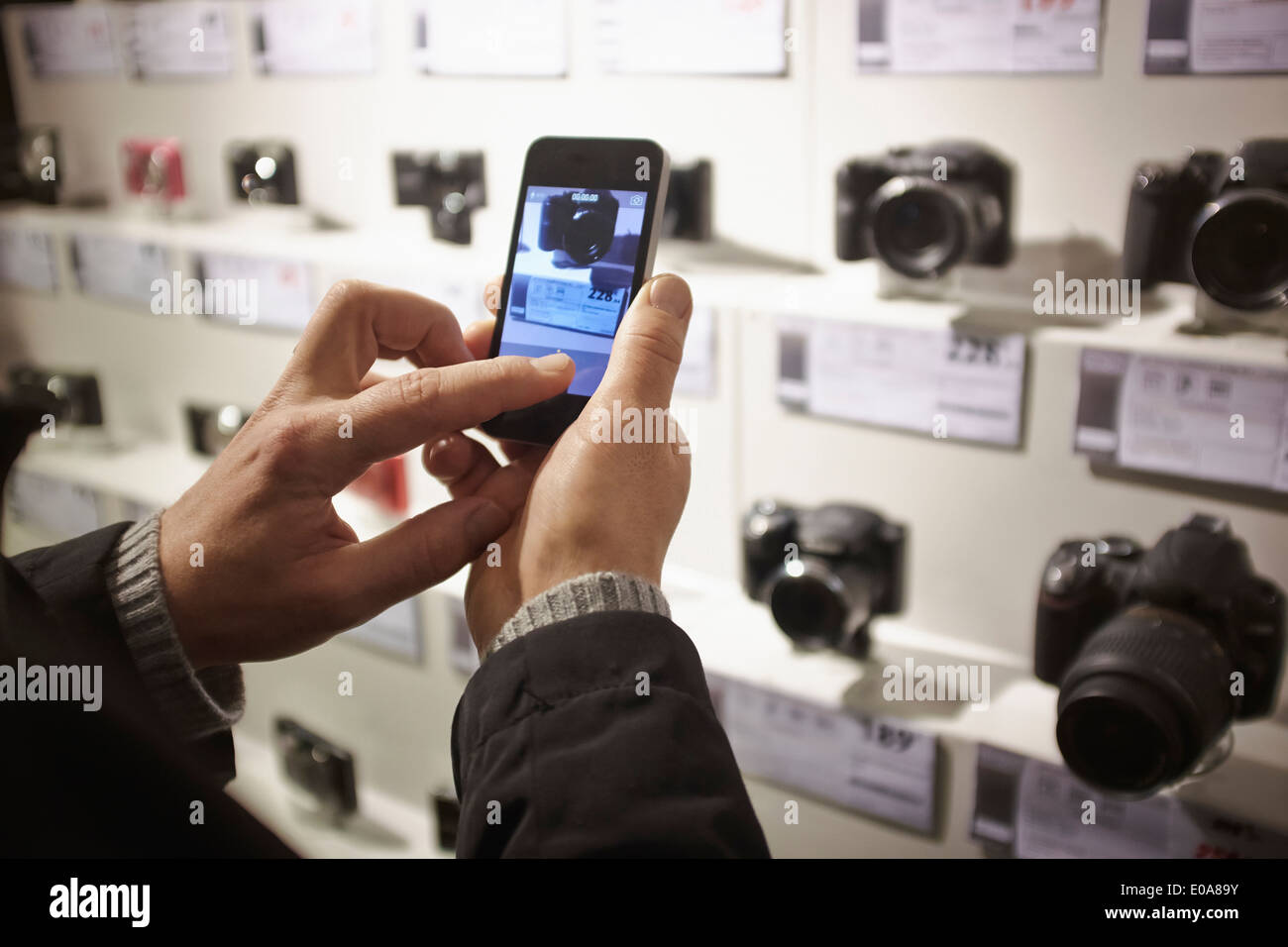 Mid adult man photographing camera's in shop display using smartphone - Stock Image