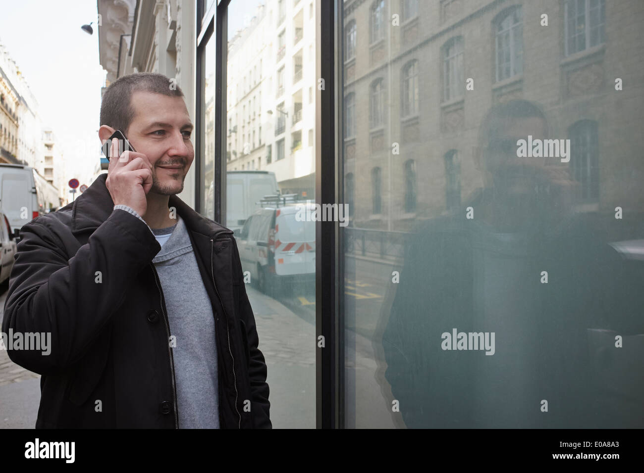 Mid adult man talking on smartphone while window shopping - Stock Image
