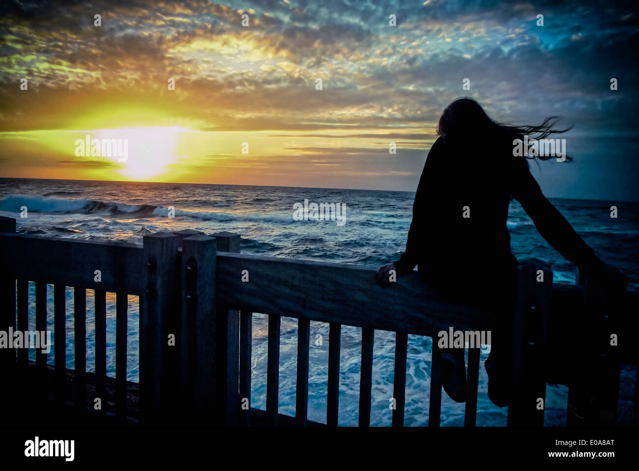 Silhouette of young woman sitting on sea front fence at dawn Stock Photo