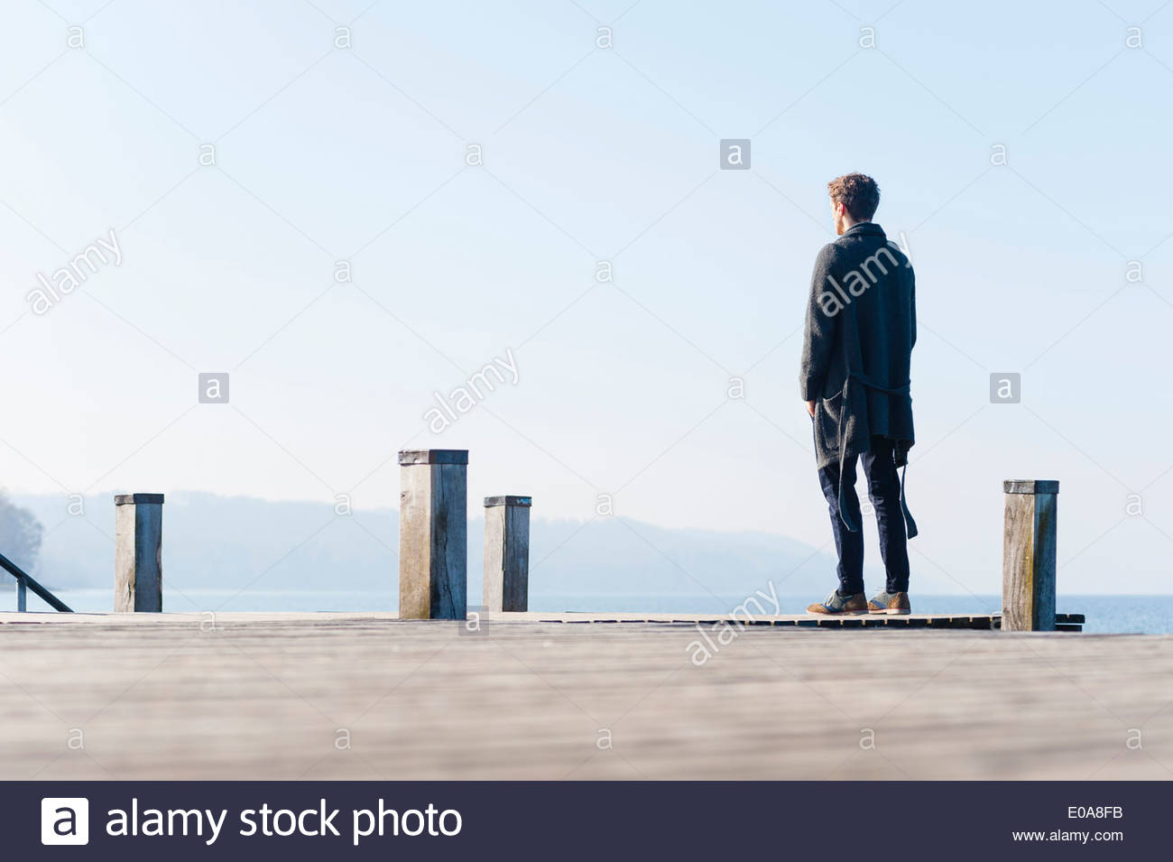 Mid adult man standing on pier, rear view - Stock Image