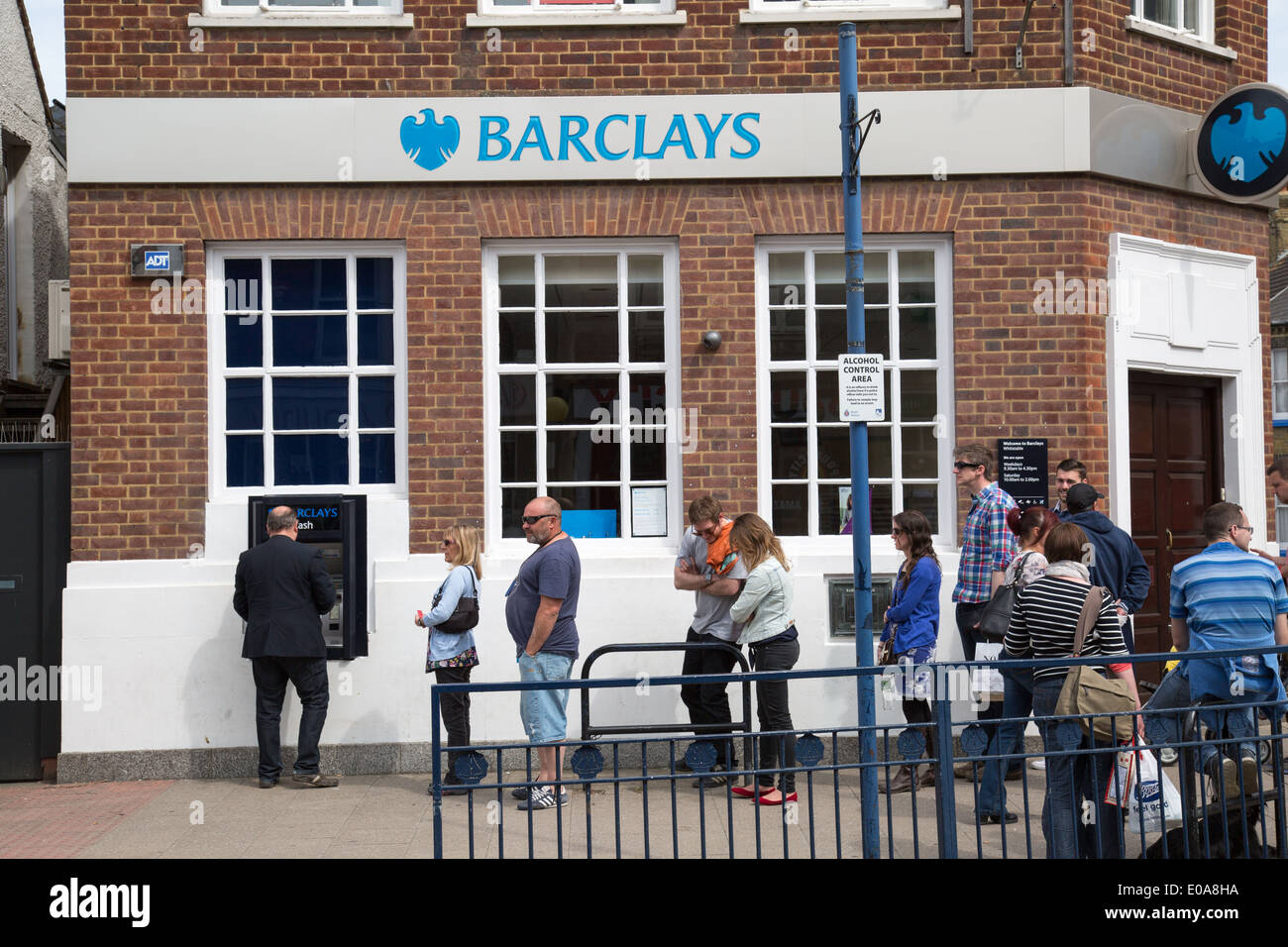 Queue for the cash dispenser at Barclays Bank seaside resort of Whitstable in Kent - Stock Image