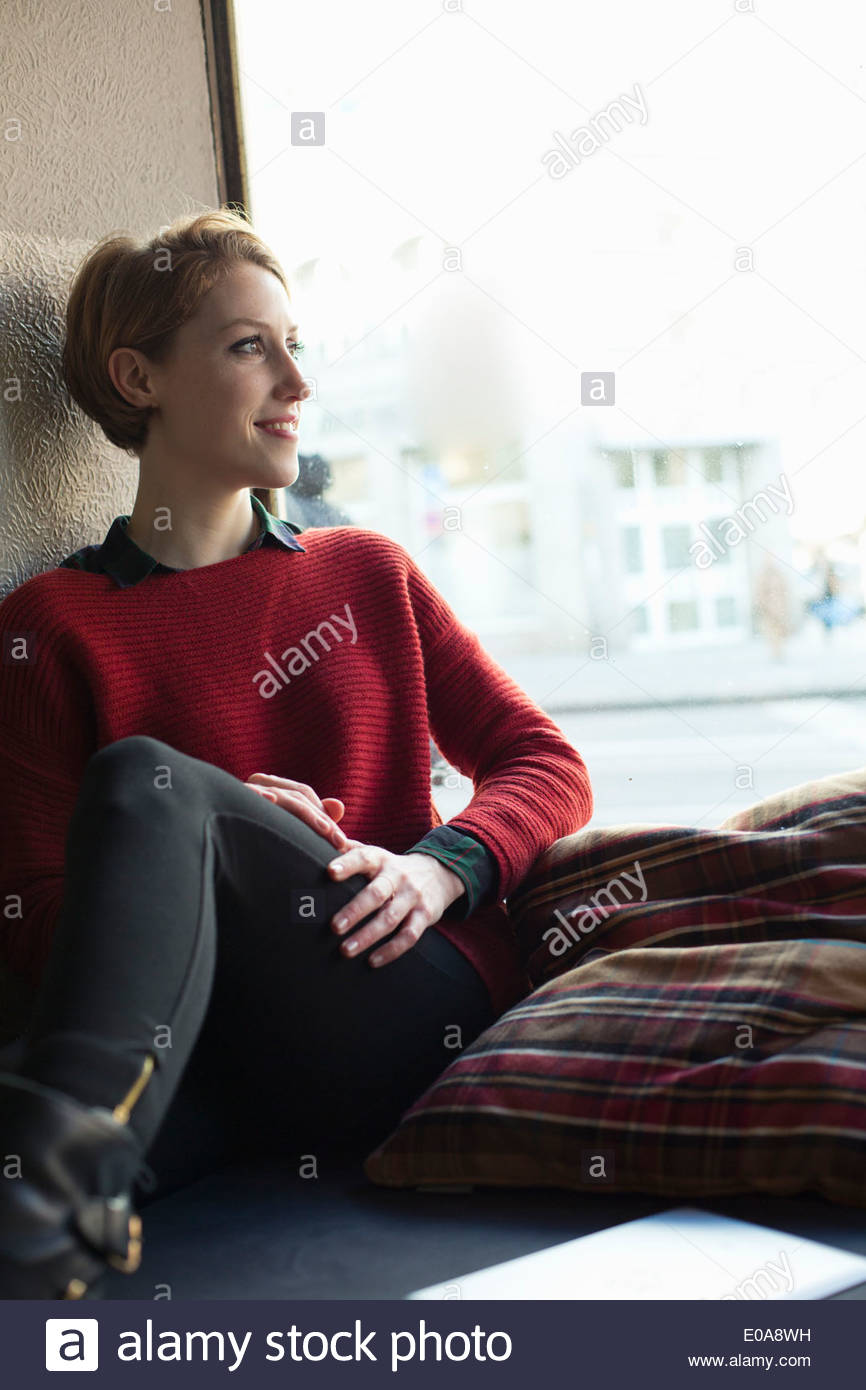 Woman sitting by window - Stock Image
