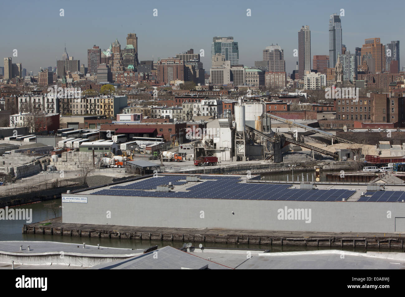 Factory building in the Gowanus Canal area with solar panels on roof with downtown Brooklyn in the background. - Stock Image