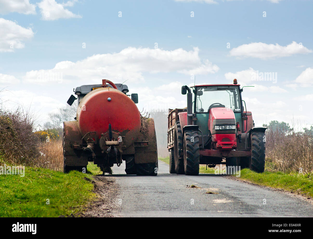 Country lane being blocked by tractors a common driving hazard during spring. - Stock Image