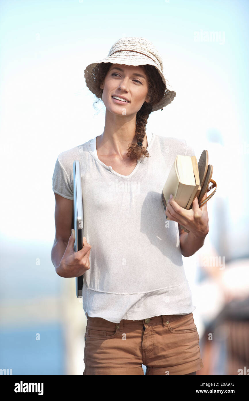 Portrait of young woman holding book, sandals and laptop - Stock Image