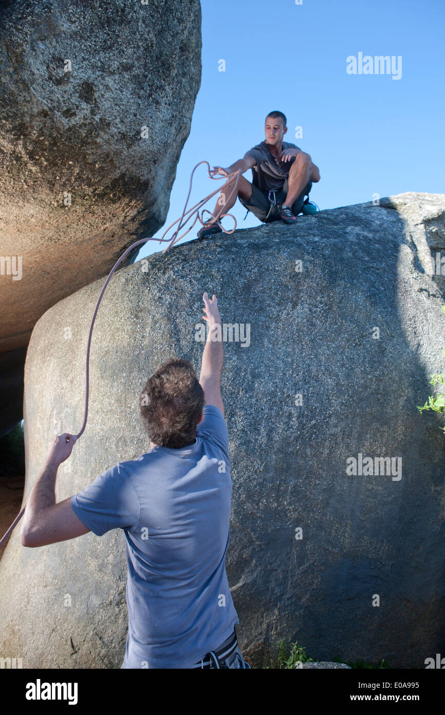 Young male climbers reaching out for each other on rock - Stock Image