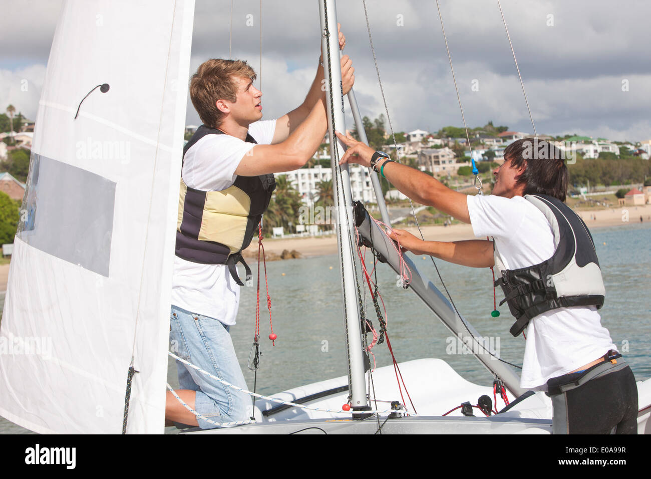 Two young men hauling up sail on boat - Stock Image