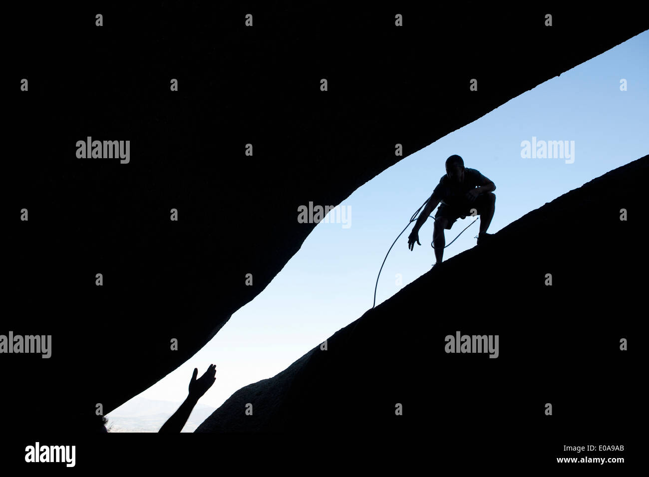 Silhouette of young male climbers reaching out for each other on rock - Stock Image