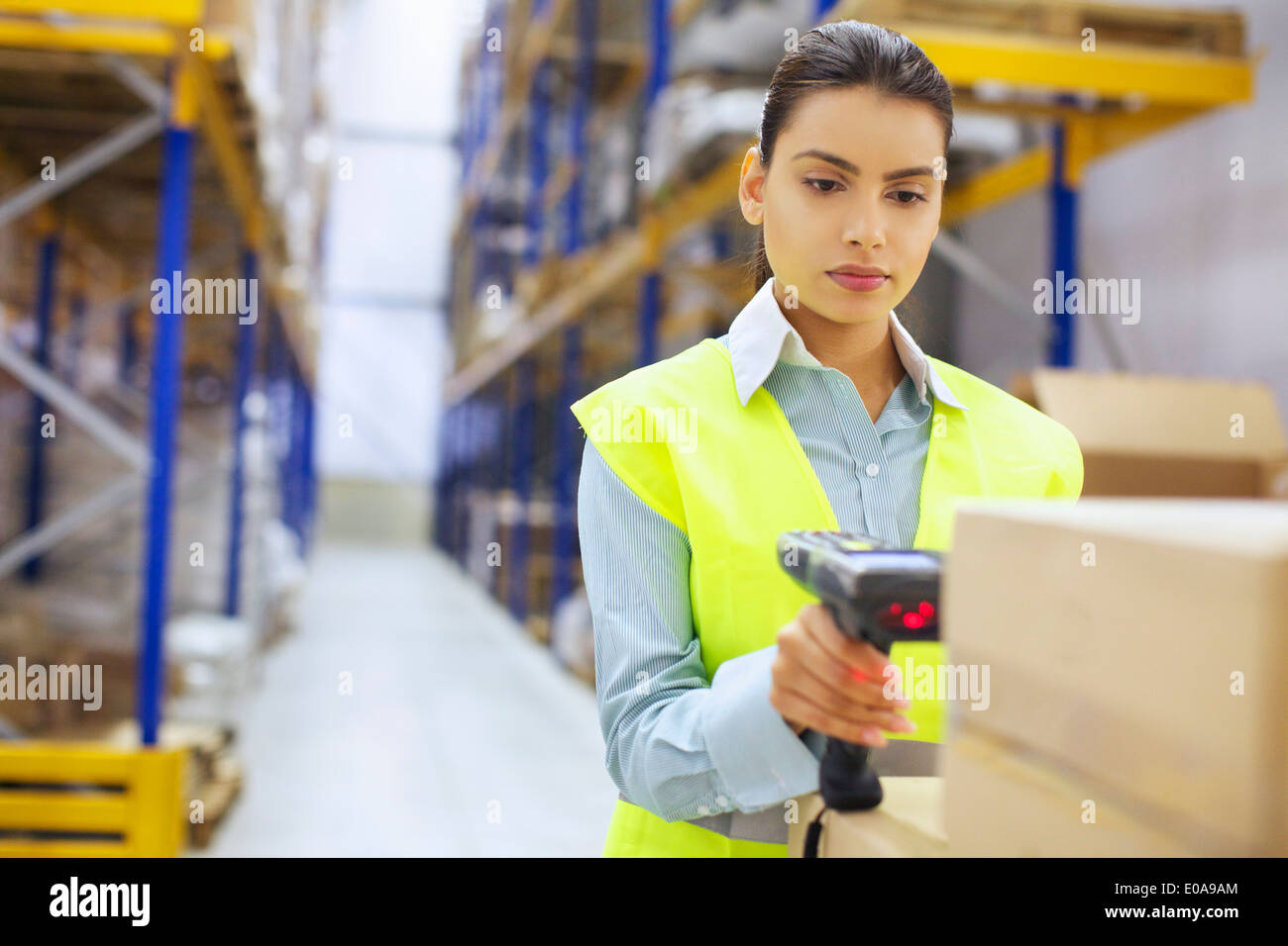 Young woman with barcode reader in distribution warehouse - Stock Image