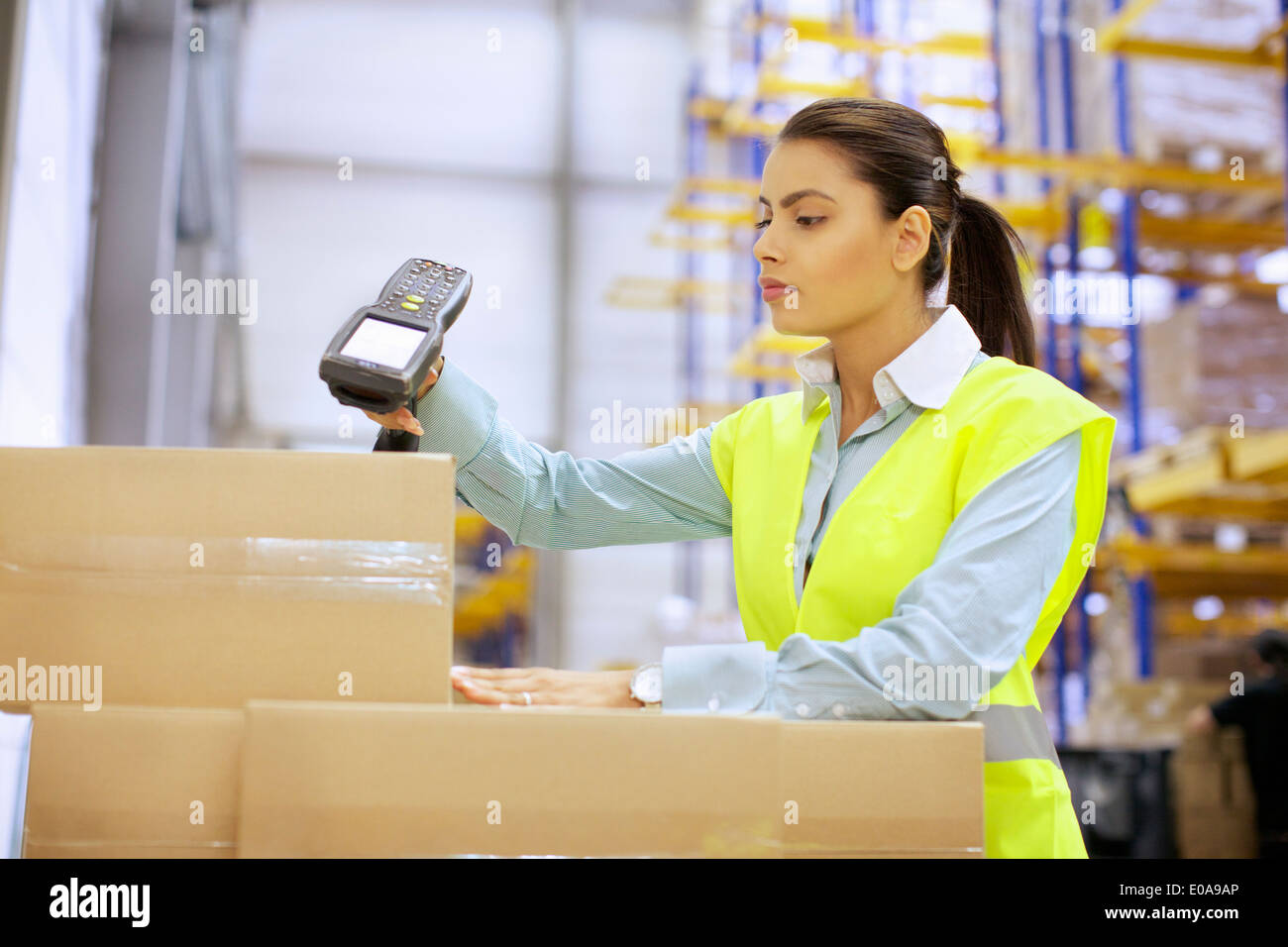 Young woman using barcode reader in distribution warehouse - Stock Image