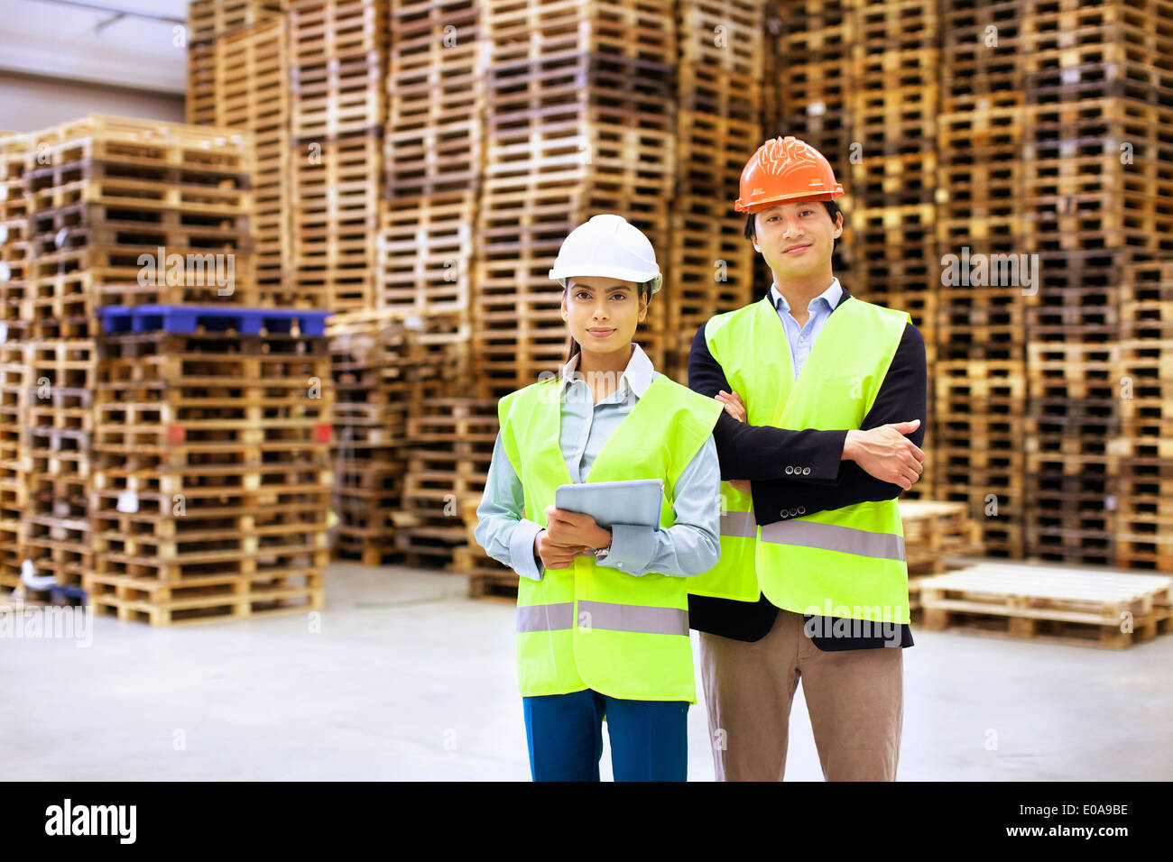 Portrait of male and female supervisors in distribution warehouse - Stock Image