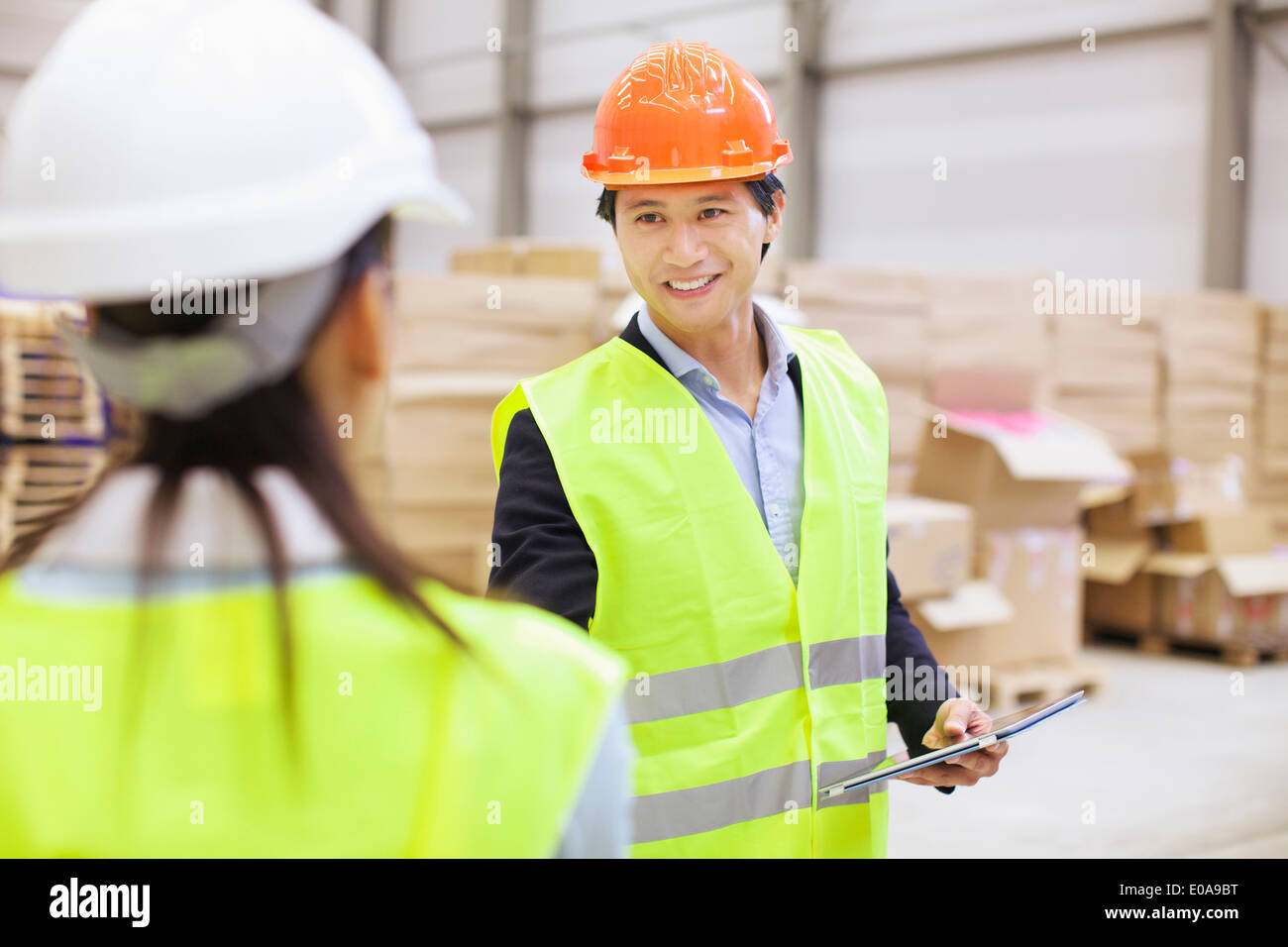Supervisor shaking hands with trainee in distribution warehouse - Stock Image