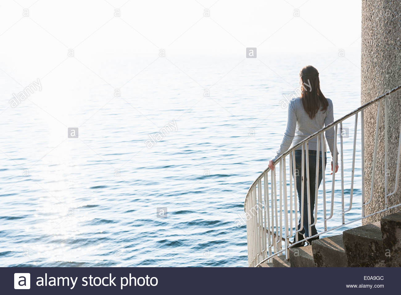 Young woman stepping down spiral stairs, Lake Constance, Lindau, Bavaria, Germany - Stock Image
