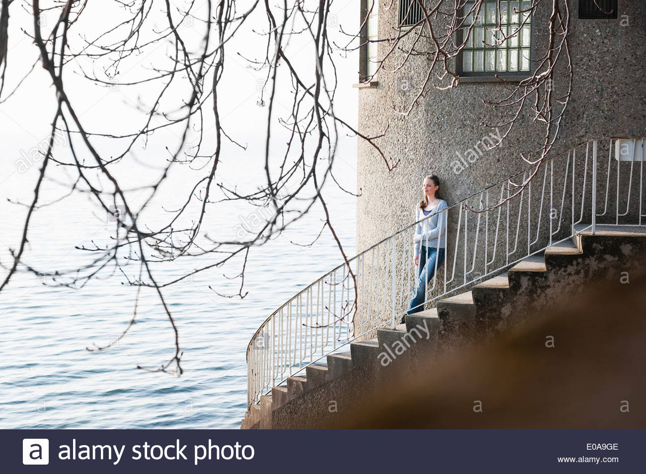 Young woman standing on spiral stairs, Lake Constance, Lindau, Bavaria, Germany - Stock Image