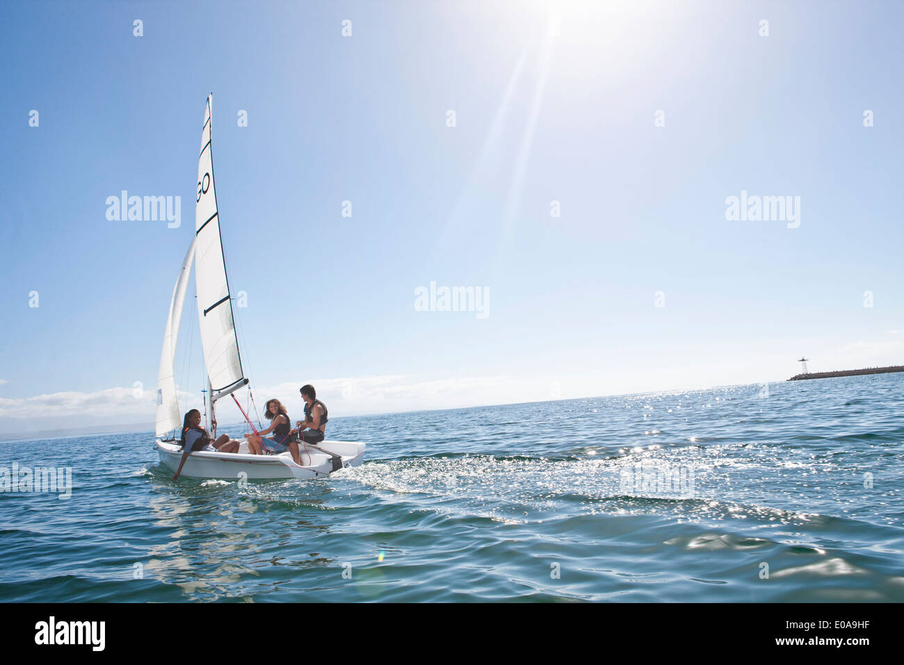 Three young friends sailing out from harbor - Stock Image