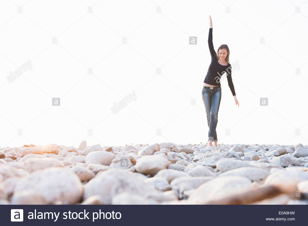 Young woman walking barefoot on stones at coast - Stock Image