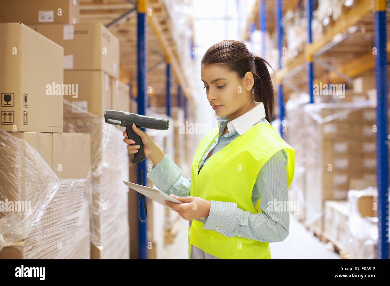 Female warehouse worker using barcode reader - Stock Image