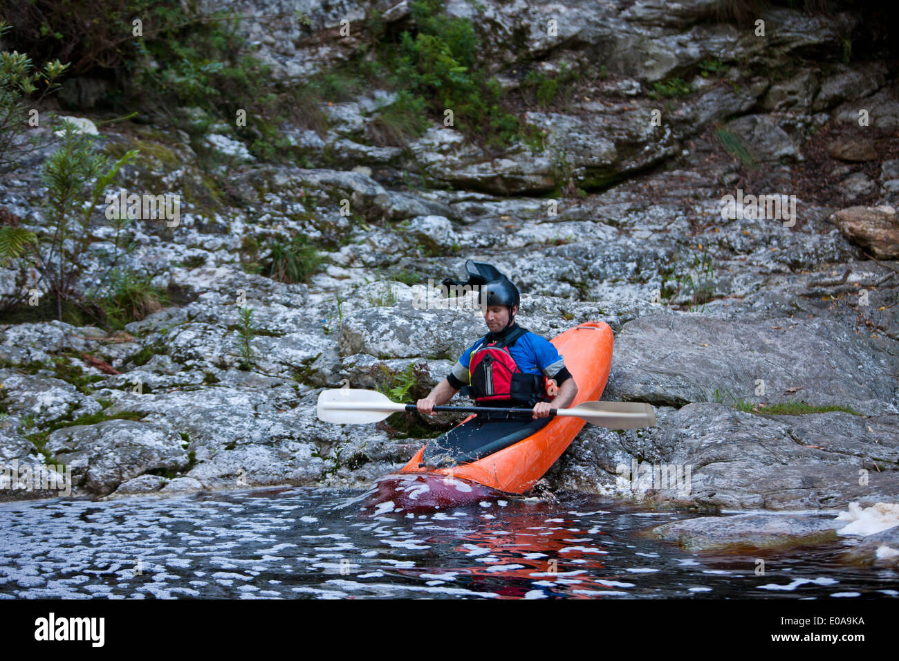 Mid adult man moving kayak from waters edge into river - Stock Image
