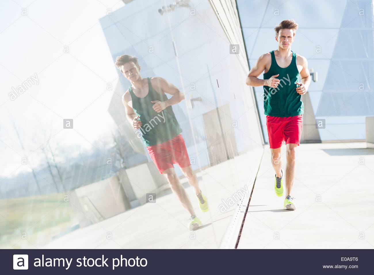 Mid adult man running past reflective window - Stock Image