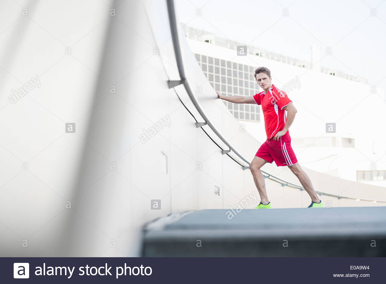 Mid adult man stretching before run - Stock Image
