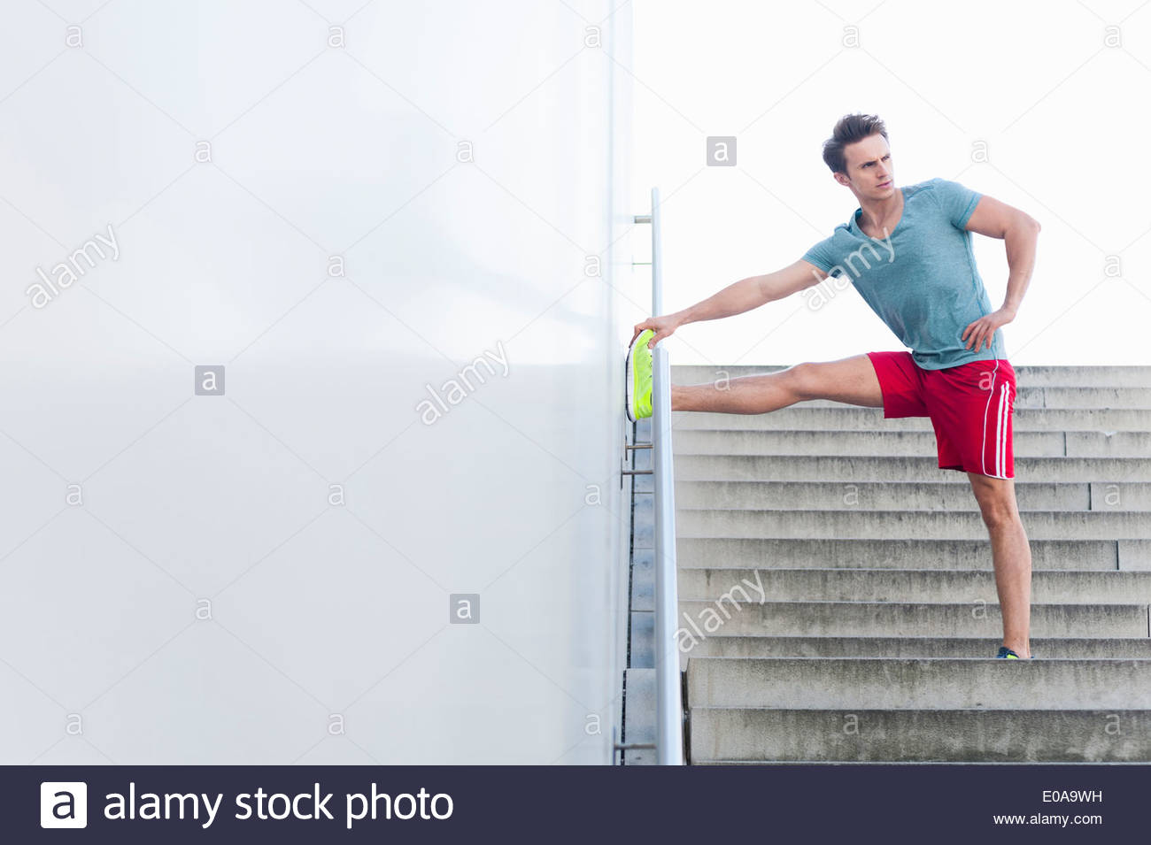 Mid adult male runner touching toe on handrail - Stock Image