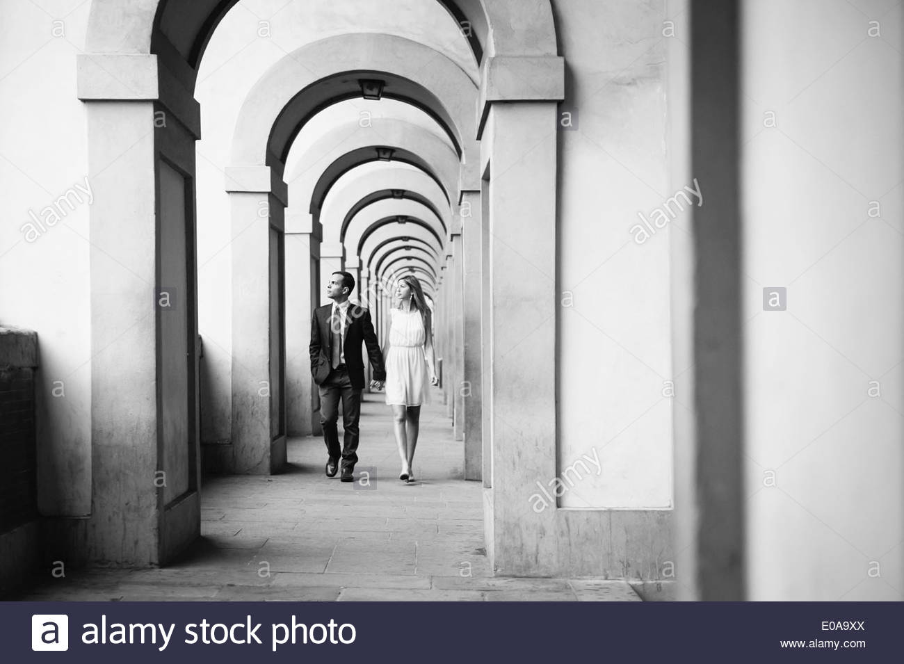 Couple walking hand in hand through arches in Florence, Tuscany, Italy - Stock Image