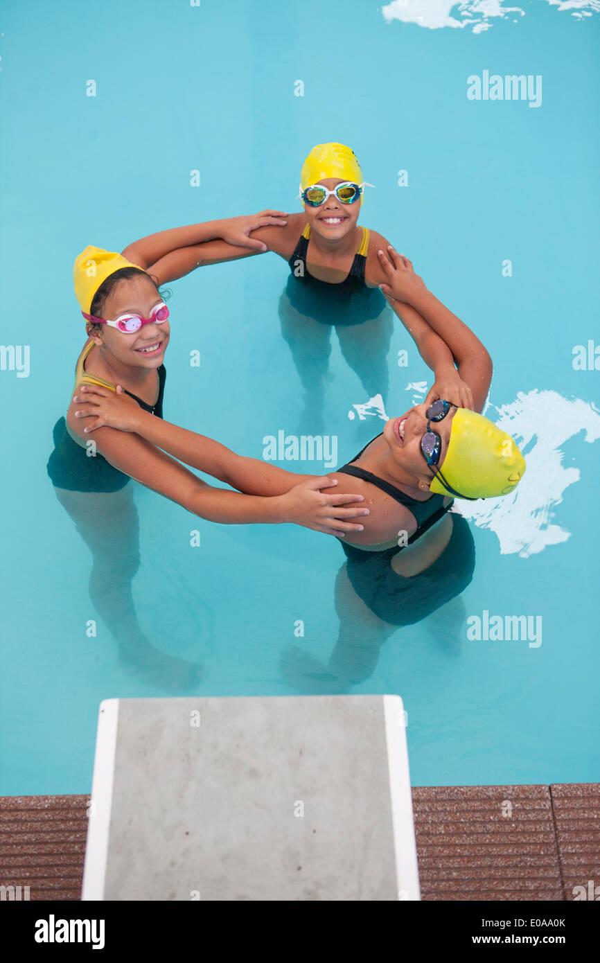 Portrait of three schoolgirl swimmers making circle - Stock Image