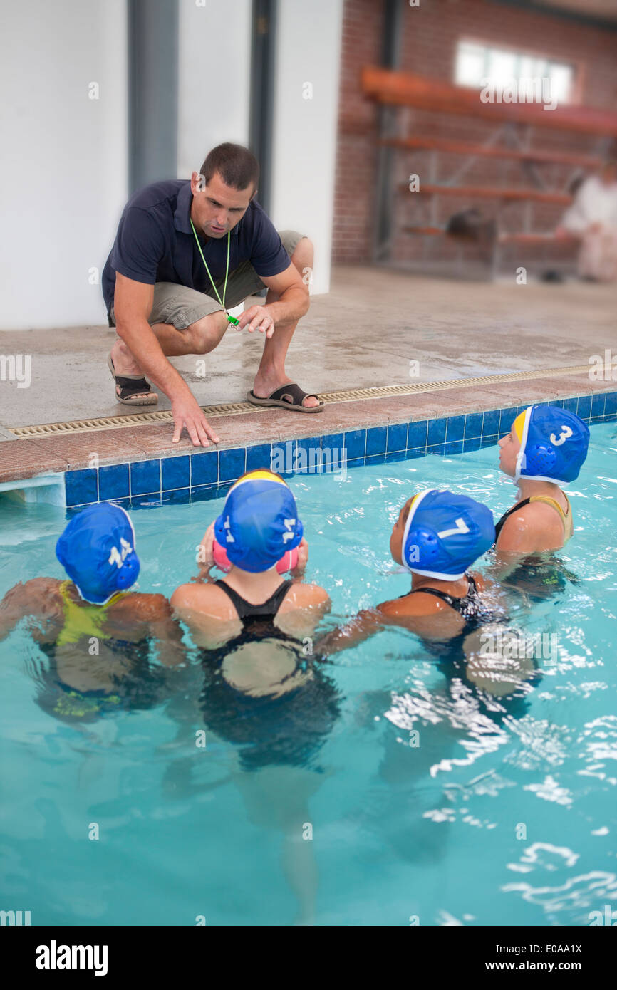 Four schoolgirl water polo players listening to teacher poolside - Stock Image