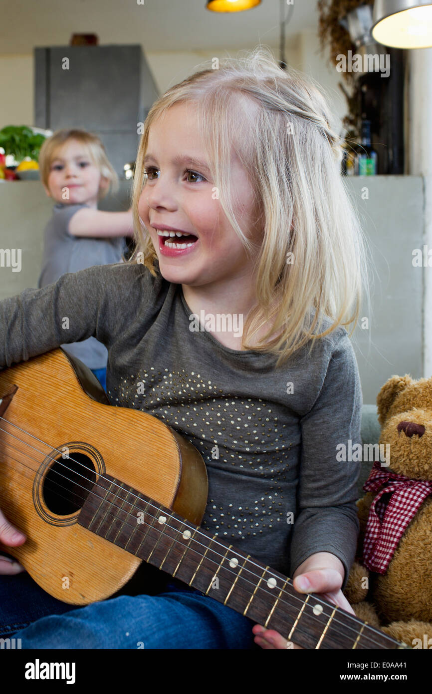 Young girl playing acoustic guitar - Stock Image