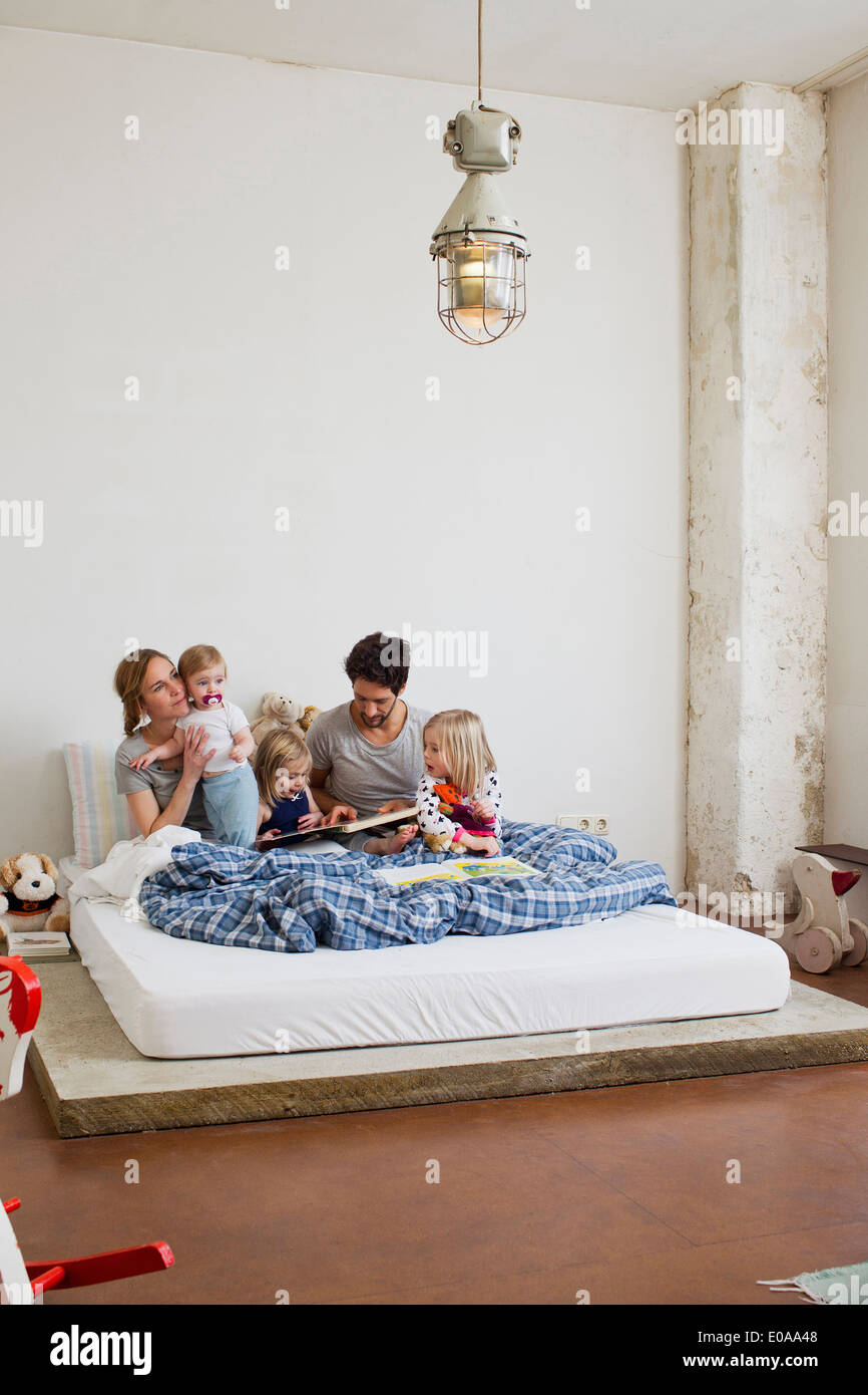 Family with three daughters reading books in bed - Stock Image