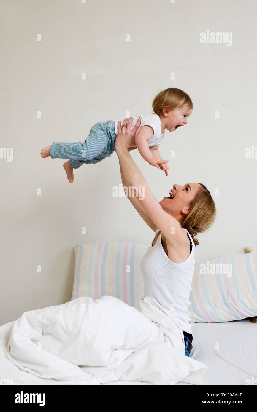 Portrait of mid adult woman holding up her one year old baby girl - Stock Image