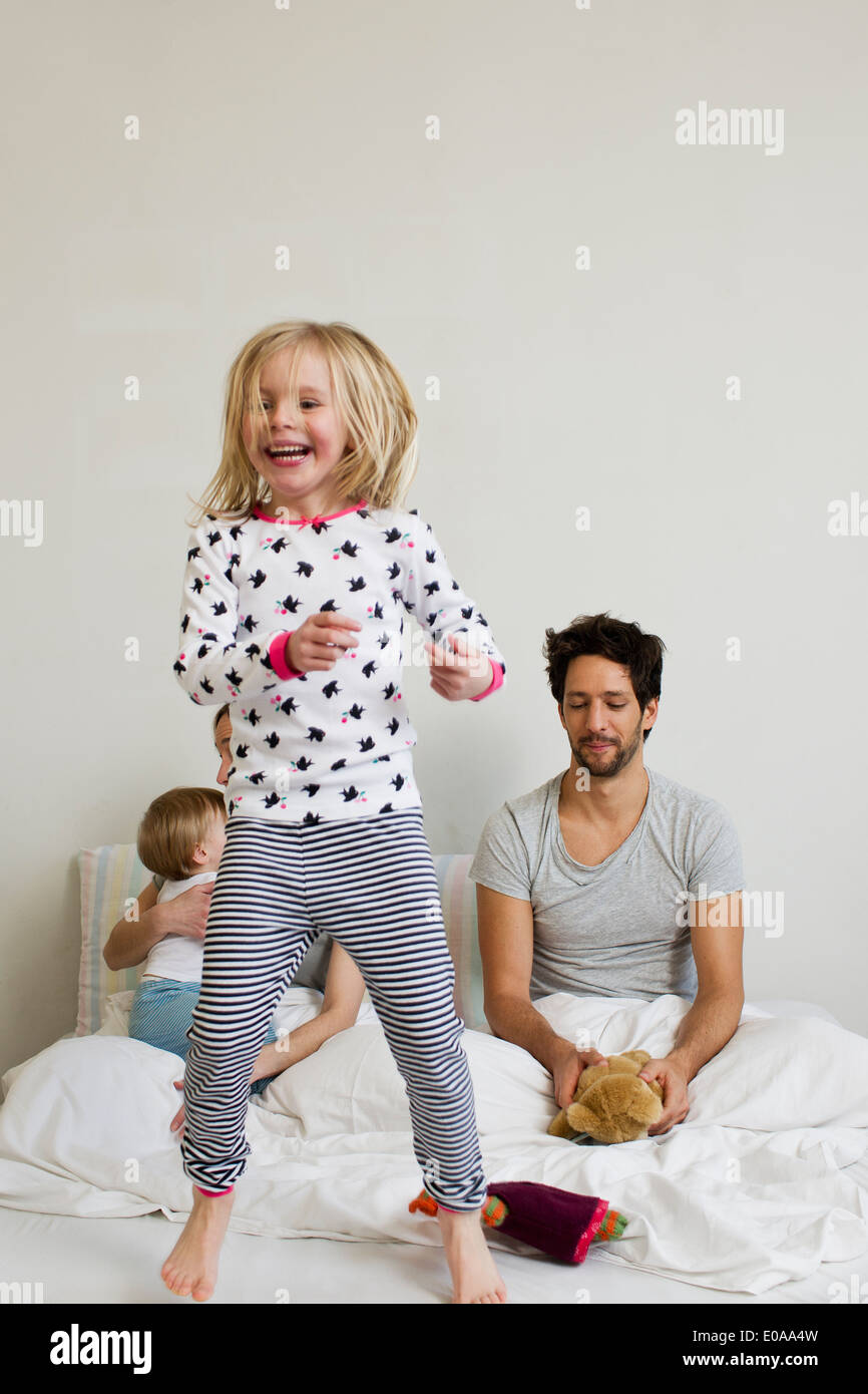 Young girl jumping on her parents bed - Stock Image