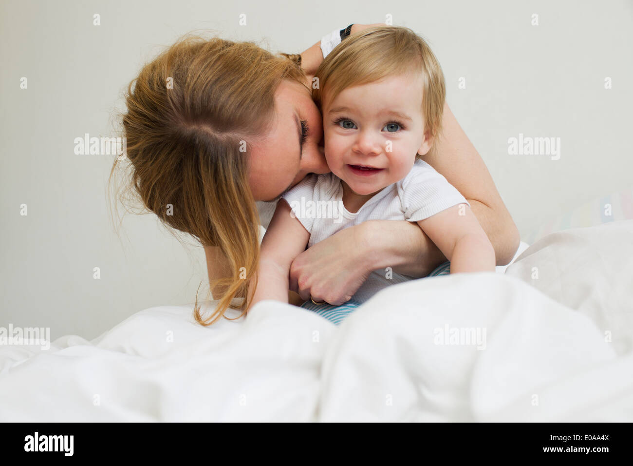 Portrait of mid adult woman hugging her year old baby girl - Stock Image
