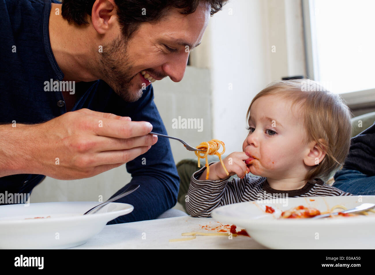 Father feeding one year old daughter spaghetti - Stock Image
