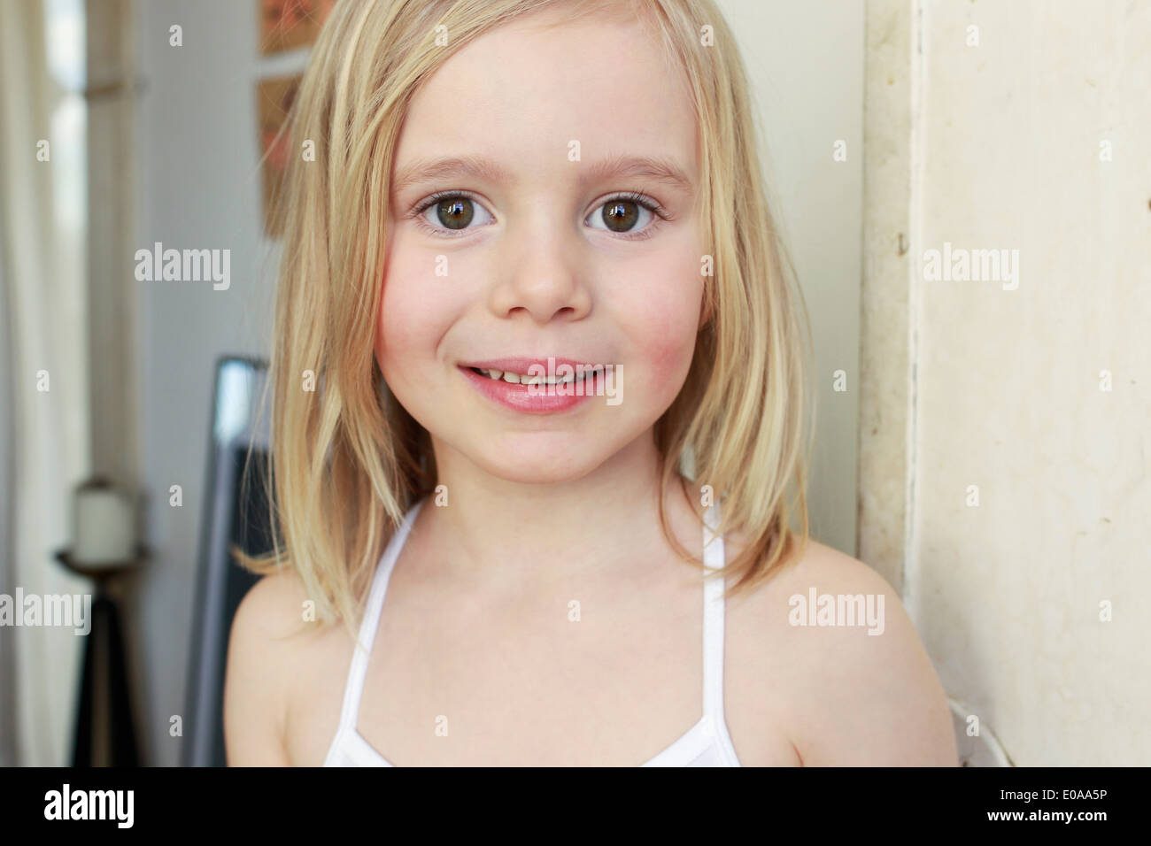 Portrait of innocent young girl in corridor - Stock Image