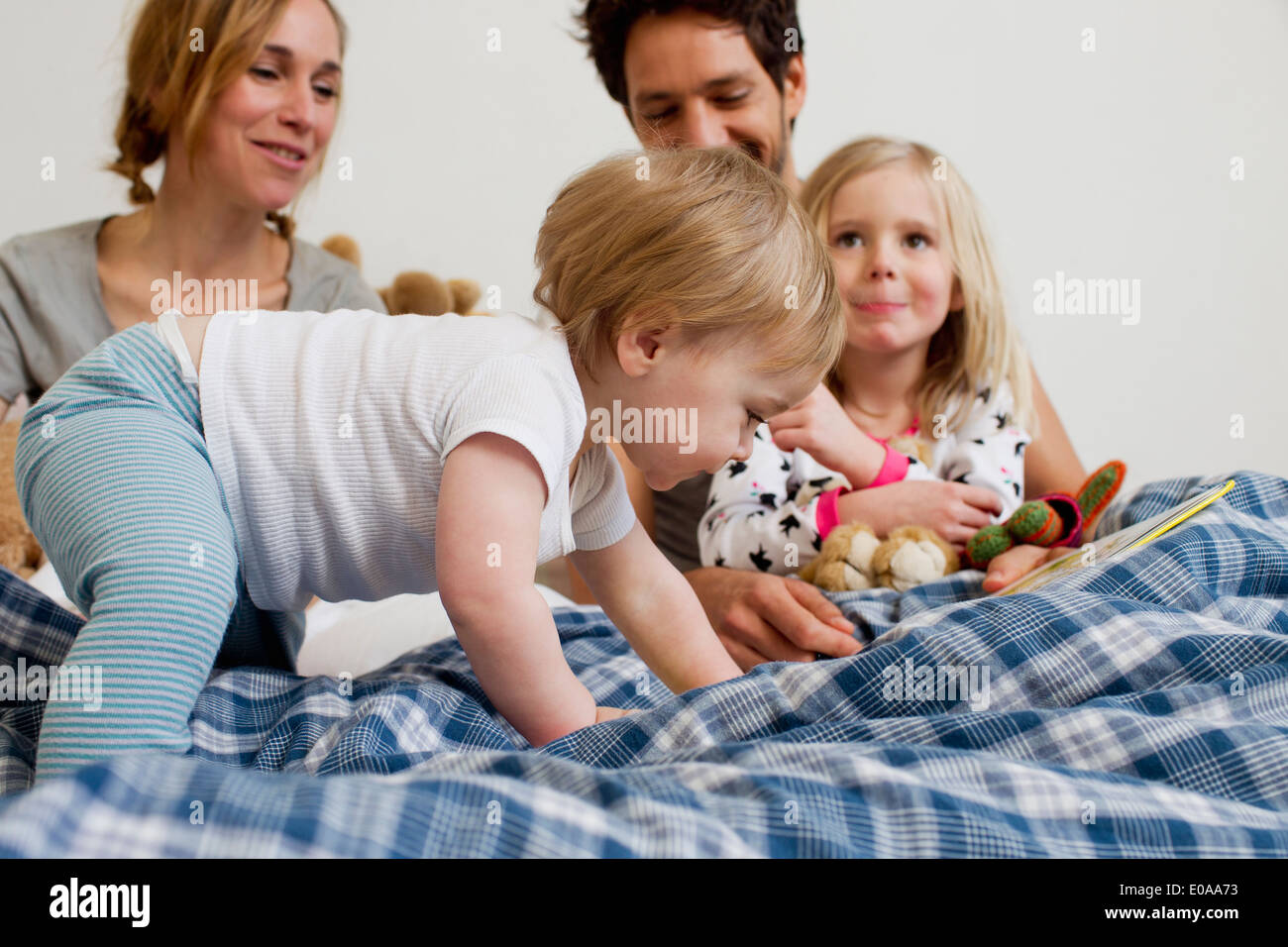 One year old baby girl crawling on parents bed - Stock Image