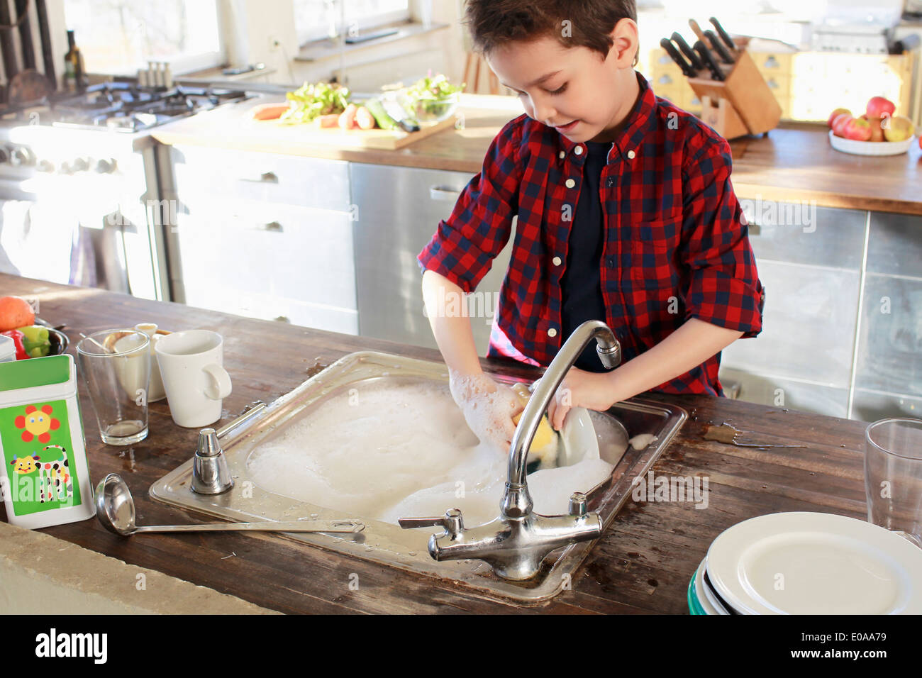 Young boy washing up in kitchen - Stock Image