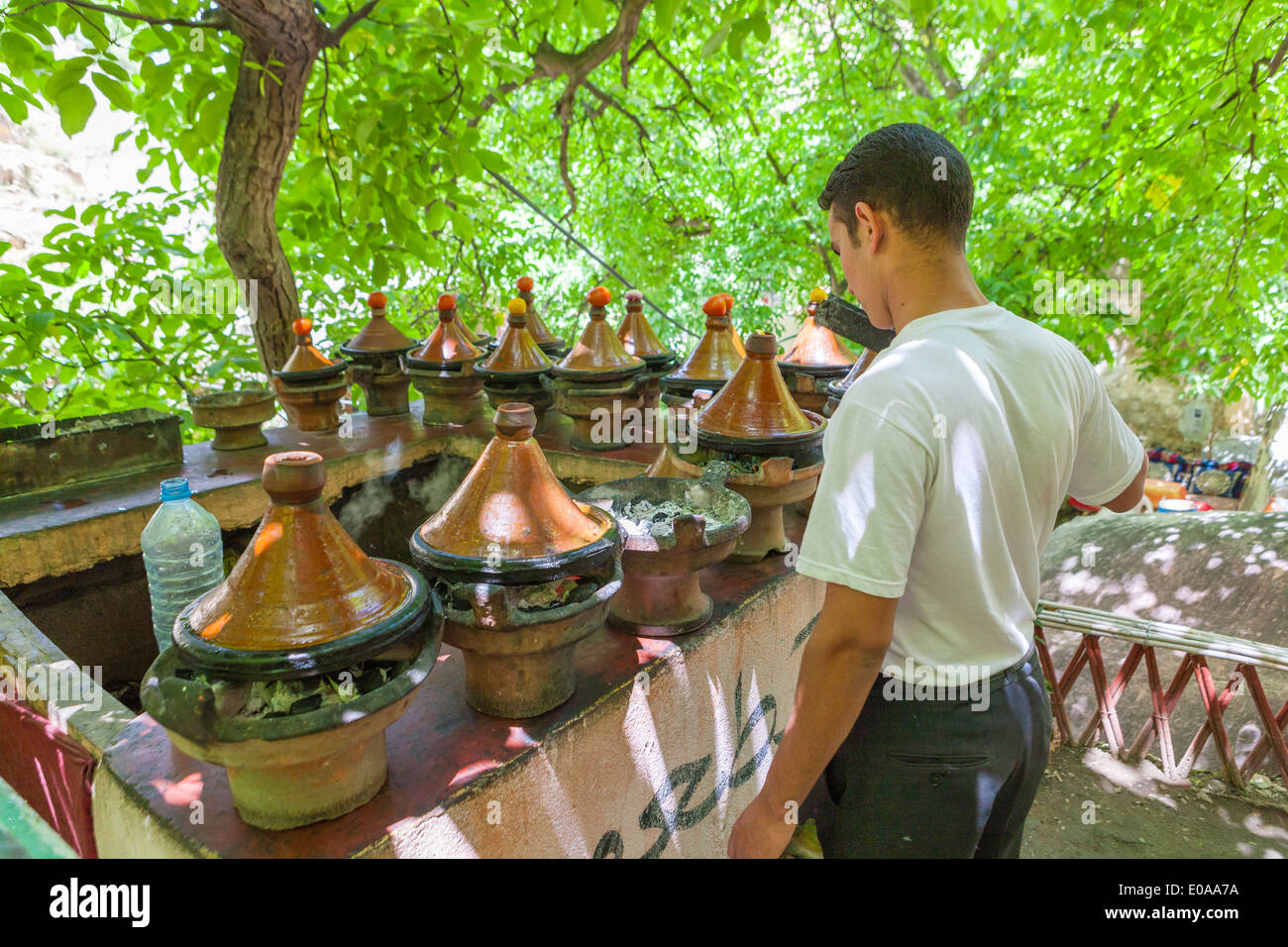 Man preparing tajine Moroccan speciality, in a typical pot, Ourika Valley, Morocco. - Stock Image