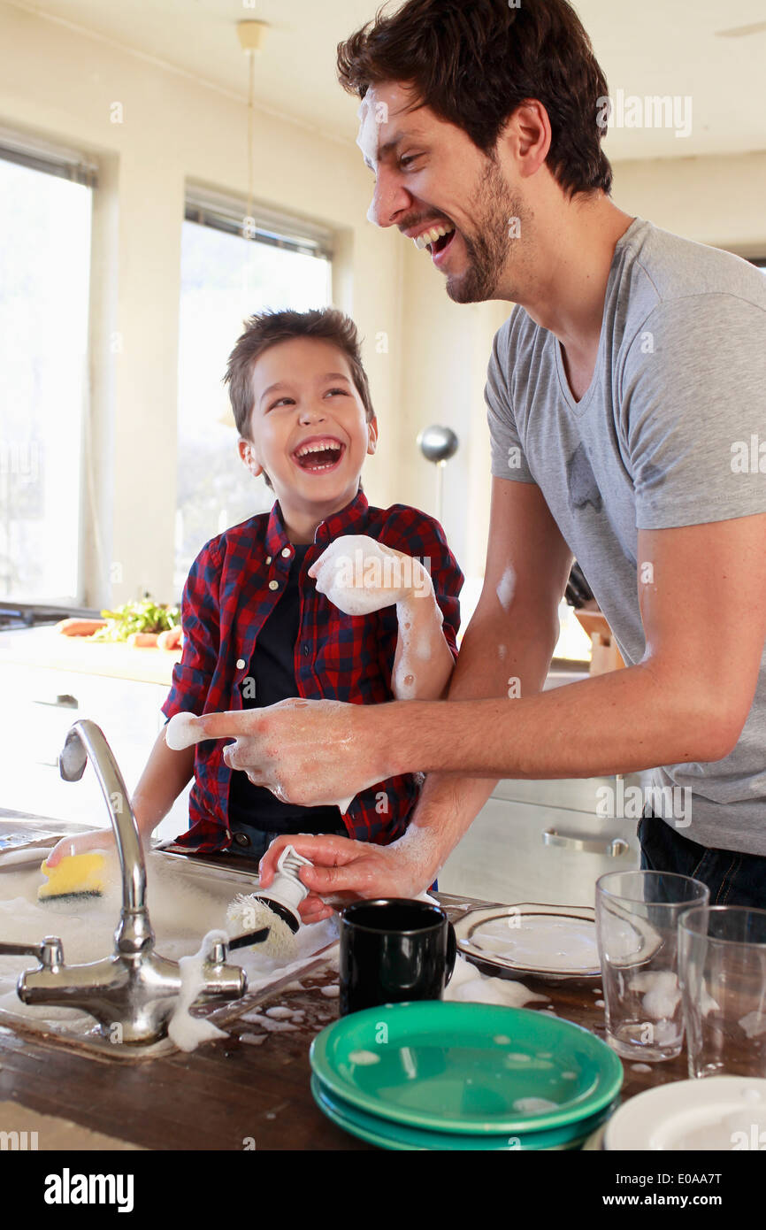 Father and son with soap suds on hands - Stock Image