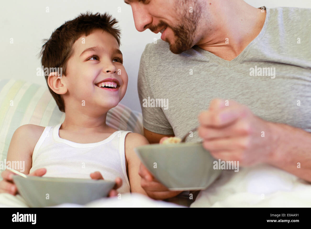 Father and young son having breakfast in bed Stock Photo