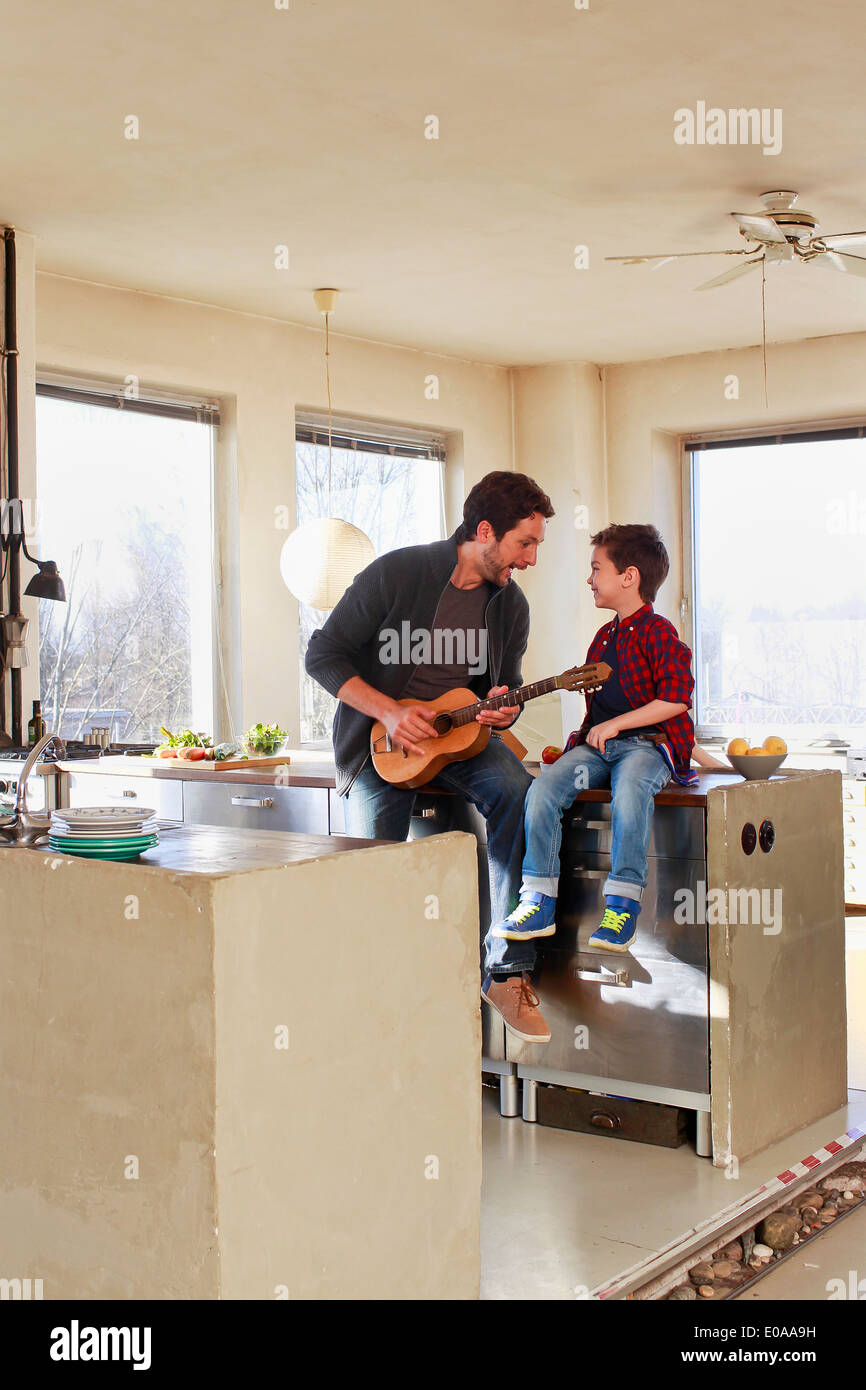 Father and young son playing guitar in kitchen - Stock Image