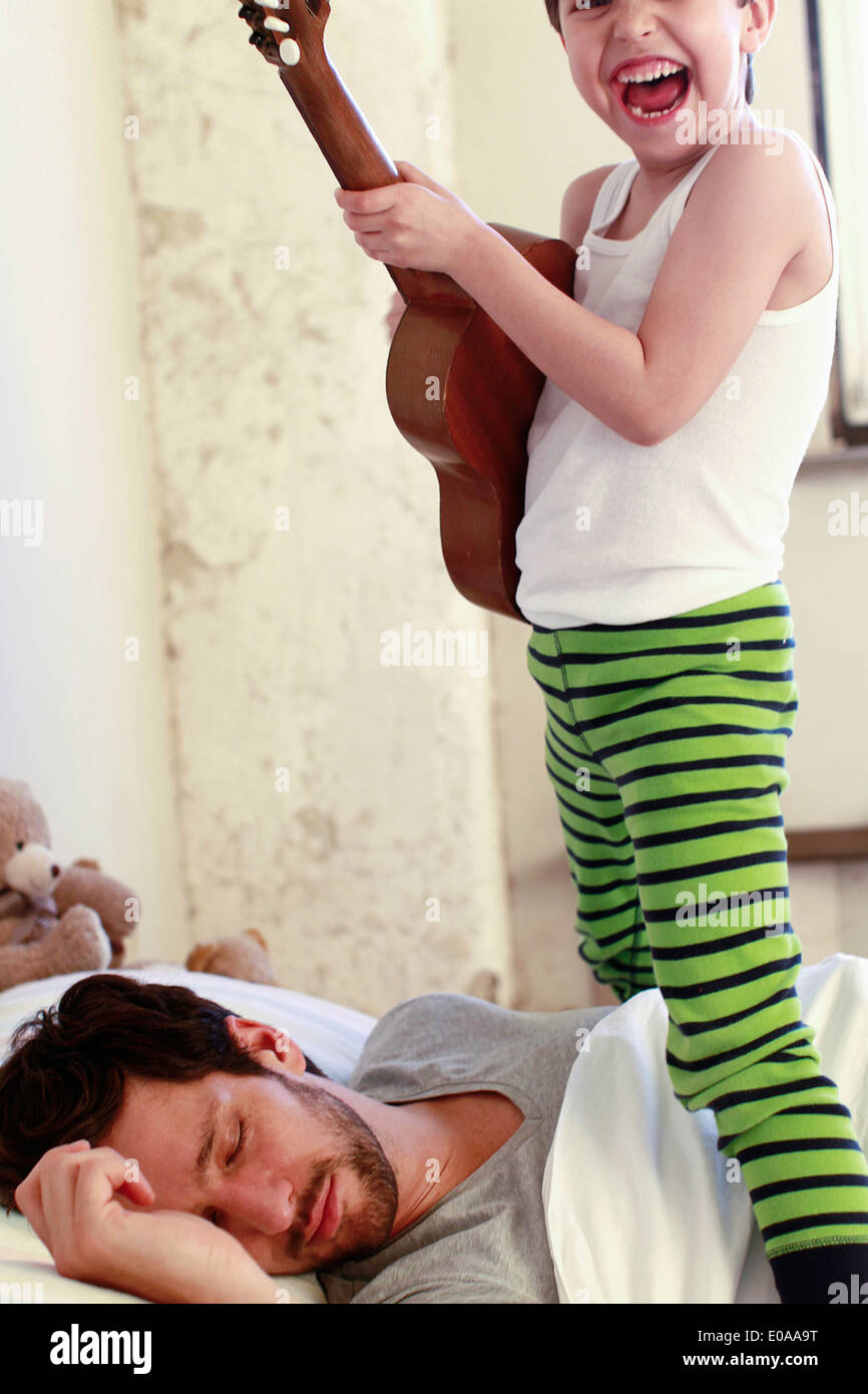 Son playing guitar whilst his father sleeps - Stock Image