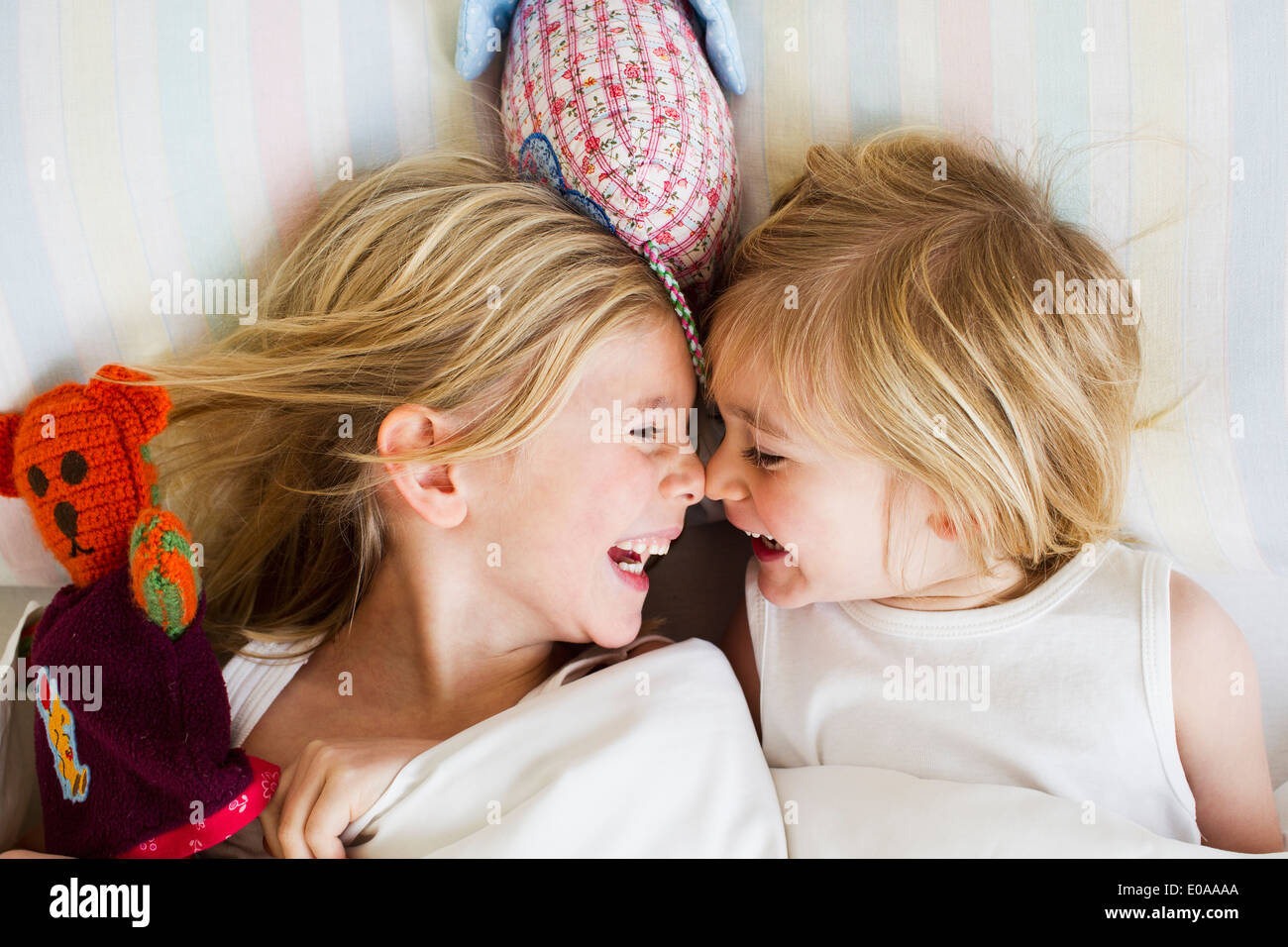 Portrait of two young sisters lying face to face in bed - Stock Image