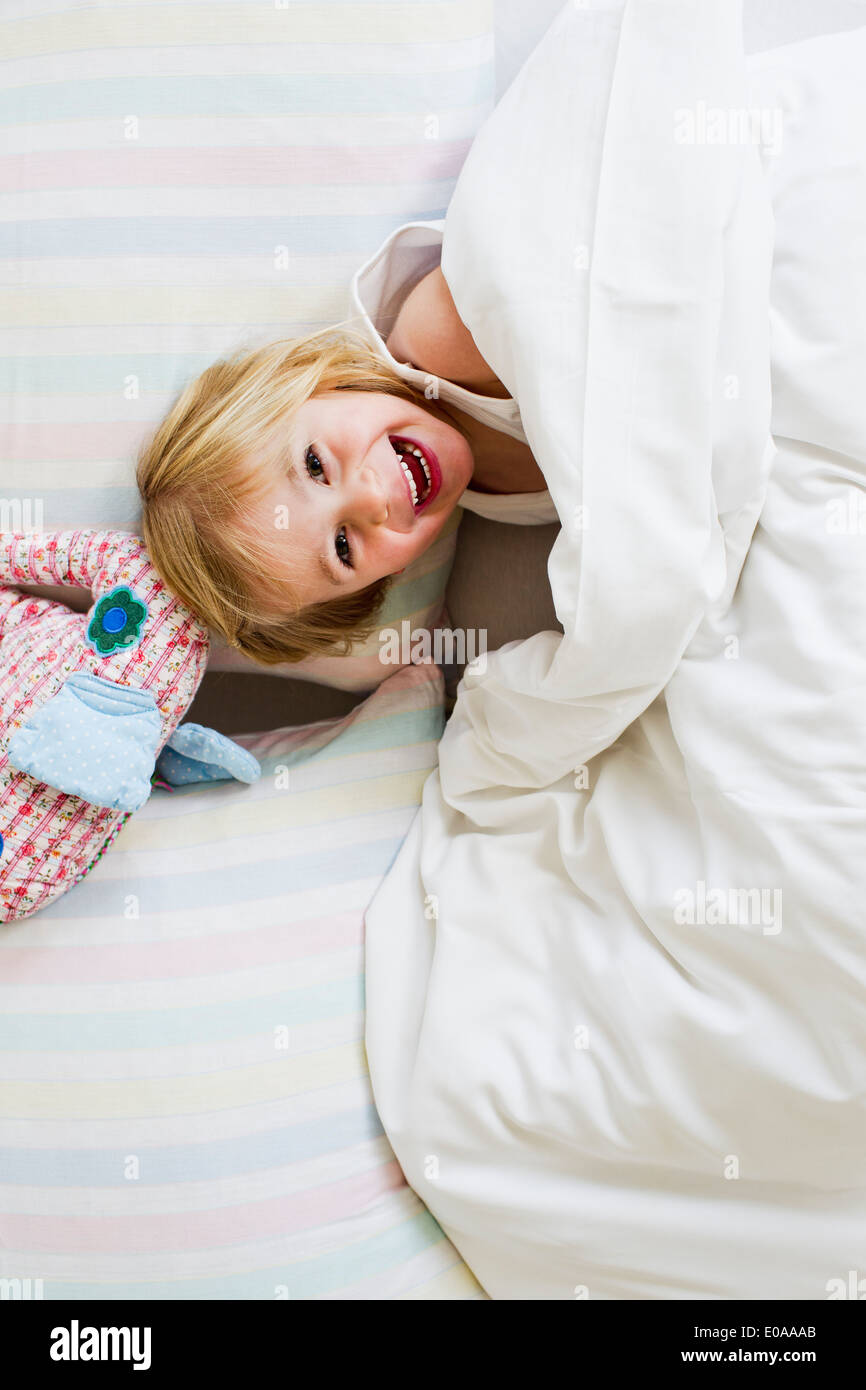 Portrait of young girl lying in bed with toy elephant - Stock Image