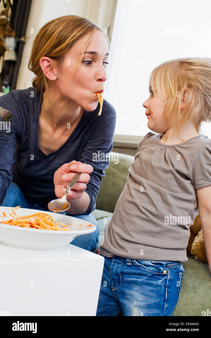 Mid adult mother eating spaghetti with her daughter - Stock Image