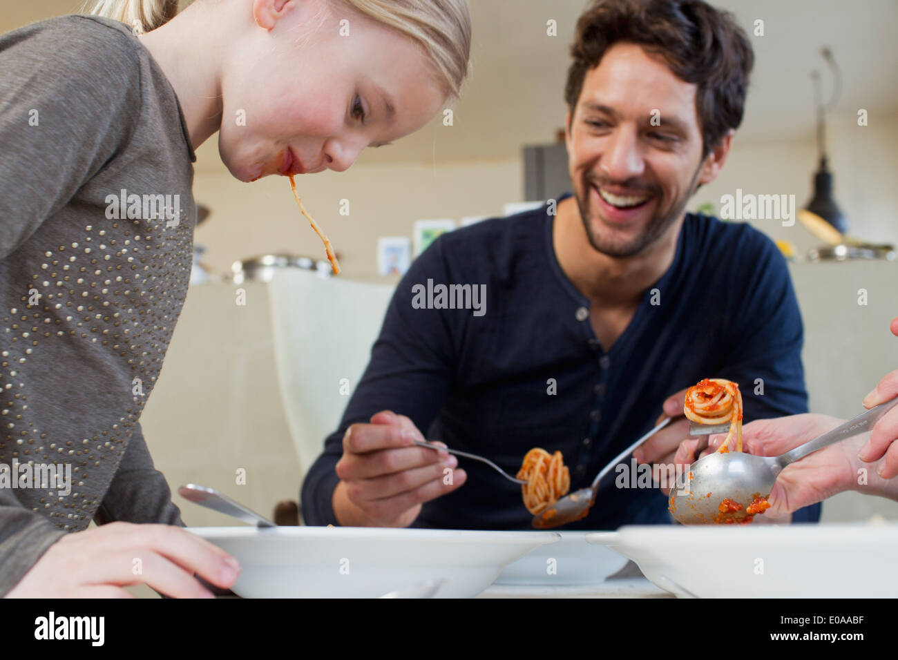 Mid adult man and family eating a spaghetti meal - Stock Image