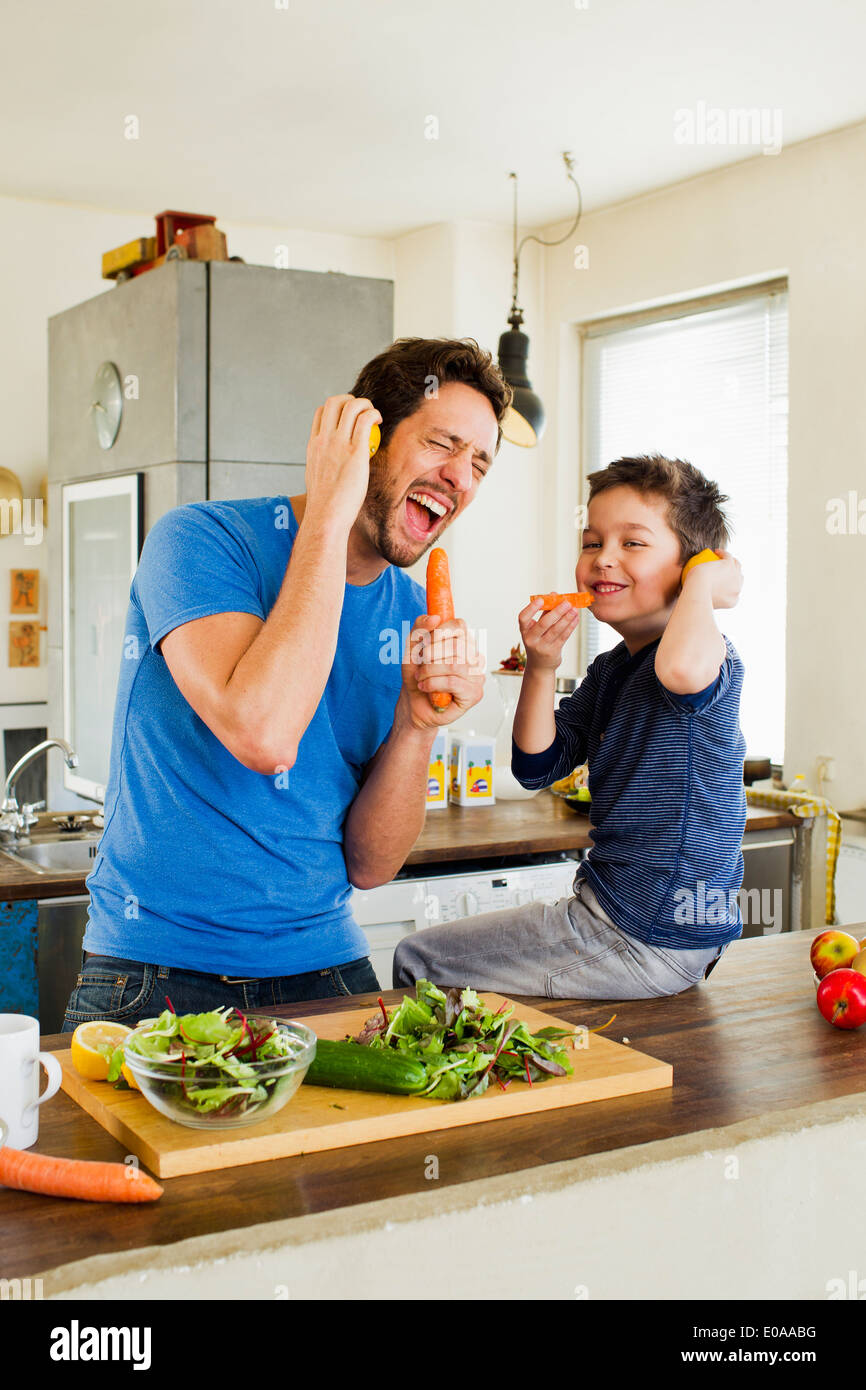 Father and young son singing into carrot microphones - Stock Image